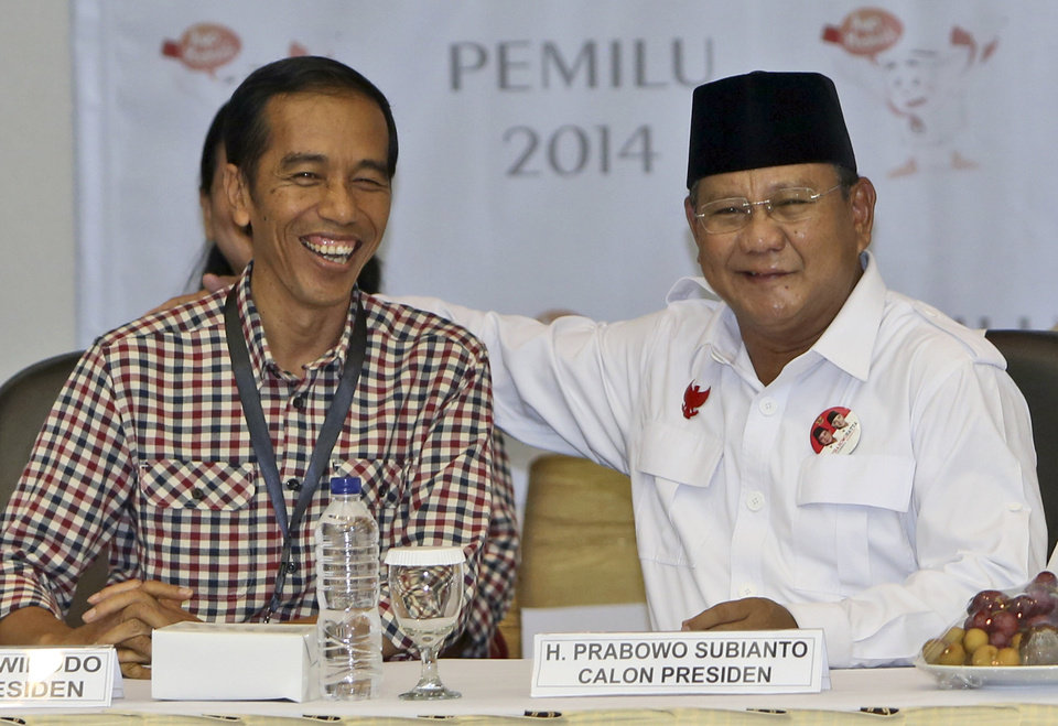 Photo - In this Sunday, June 1, 2014 file photo, Indonesian presidential candidates, former special forces commander Prabowo Subianto, right, and Jakarta Governor Joko Widodo share a light moment prior to drawing the electoral number that will represent them in the upcoming presidential election in Jakarta, Indonesia. As the world's third-largest democracy prepares to head to the polls on Wednesday, July 8, 2014, the country remains fiercely divided as the common man and the military man slug it out in a race once considered a sure thing, but now way too close to call. (AP Photo/Tatan Syuflana, File)