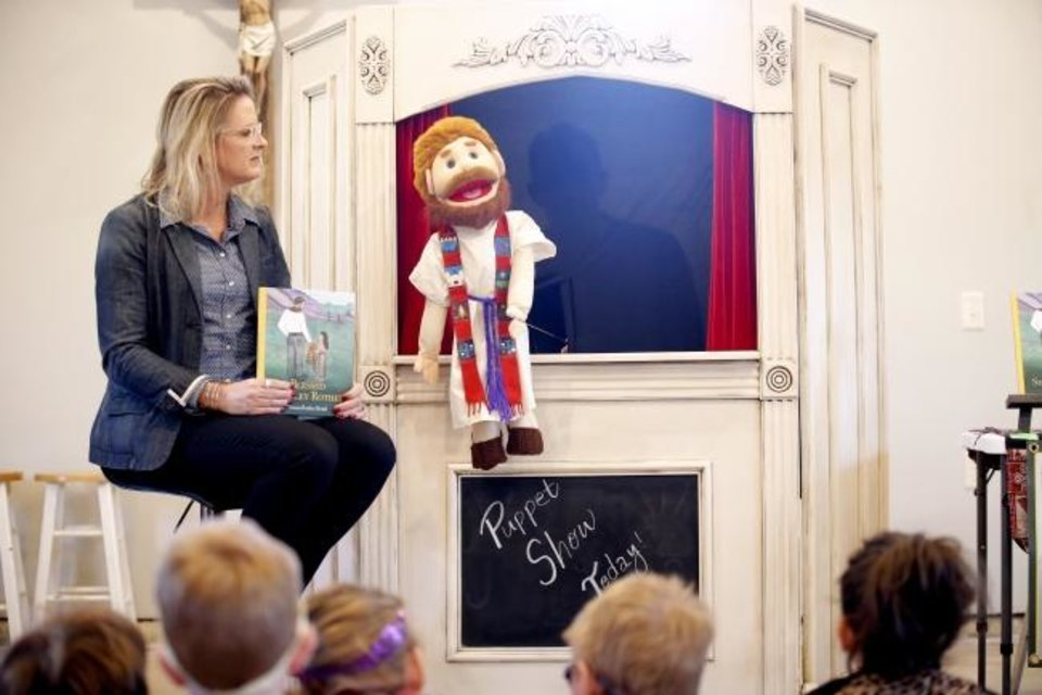 Photo -  Norman author Susan Rother Bond watches as the story of Blessed Stanley Rother is represented in a puppet show at the Gospel of Life Dwelling in Moore. [Sarah Phipps/The Oklahoman]
