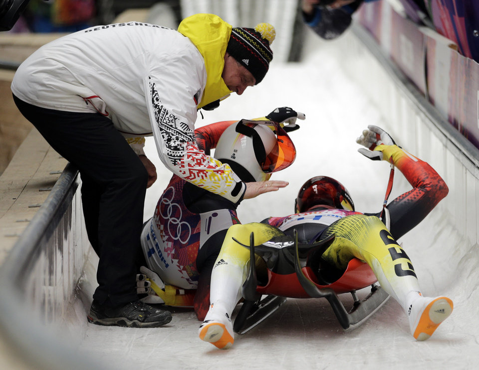 Photo - The doubles team of Tobias Wendl and Tobias Arlt from Germany celebrate in the finish area after their final run to win the gold medal during the men's doubles luge at the 2014 Winter Olympics, Wednesday, Feb. 12, 2014, in Krasnaya Polyana, Russia.(AP Photo/Jae C. Hong)