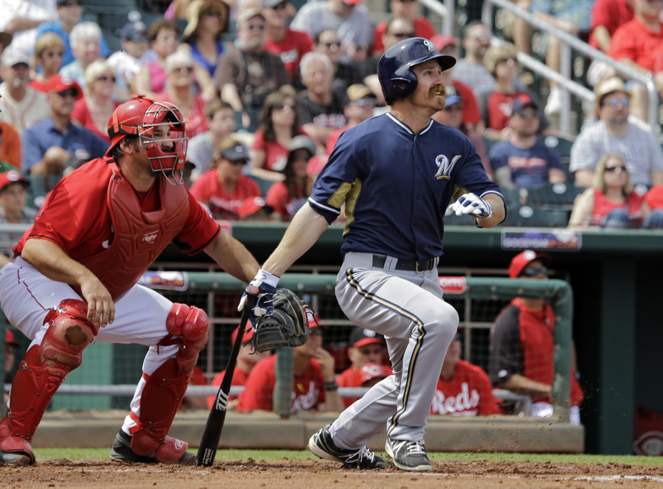 Photo - Milwaukee Brewers' Kevin Mattison hits a two-run double as Cincinnati Reds catcher Corky Miller watches, left, in the second inning of a spring exhibition baseball game Sunday, March 23, 2014, in Goodyear, Ariz. (AP Photo/Mark Duncan)