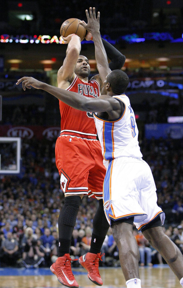 Chicago Bulls forward Carlos Boozer shoots over Oklahoma City Thunder forward Serge Ibaka during the first quarter of an NBA basketball game in Oklahoma City, Sunday, Feb. 24, 2013. (AP Photo/Alonzo Adams)