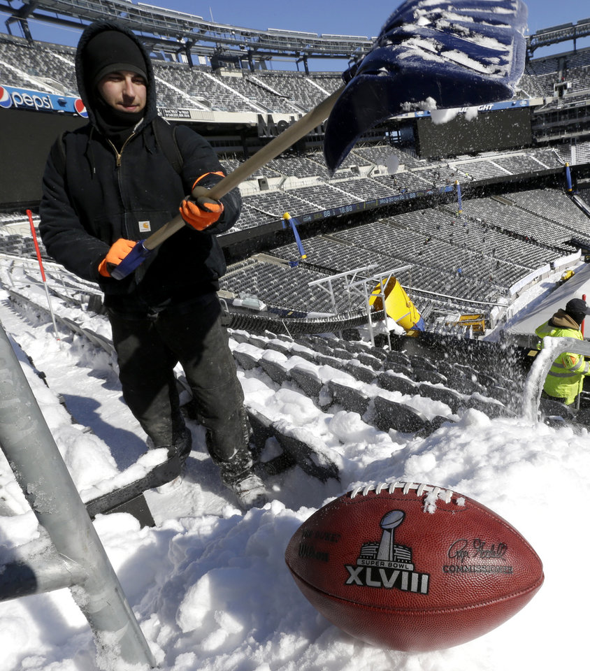 Photo - A football with the Super Bowl XLVIII logo is set on a mound of snow as an for an NFL photographer to make photos of it as workers shovel snow off the seating area at MetLife Stadium as crews removed snow ahead of Super Bowl XLVIII following a snow storm, Wednesday, Jan. 22, 2014, in East Rutherford, N.J. Super Bowl XLVIII, which will be played between the Denver Broncos and the Seattle Seahawks on Feb. 2, will be the first NFL title game held outdoors in a city where it snows. (AP Photo/Julio Cortez)