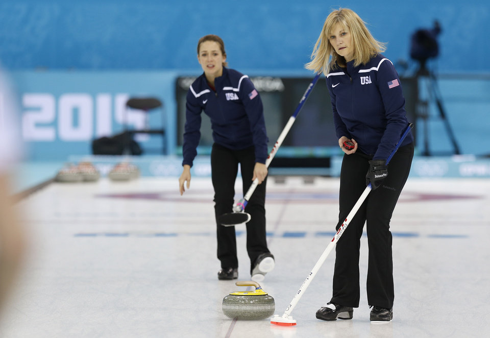 Photo - Team USA skip Erika Brown, right, uses a stopwatch to time the throw from teammate Jessica Schultz during the first day of curling training at the 2014 Winter Olympics, Saturday, Feb. 8, 2014, in Sochi, Russia. (AP Photo/Robert F. Bukaty)