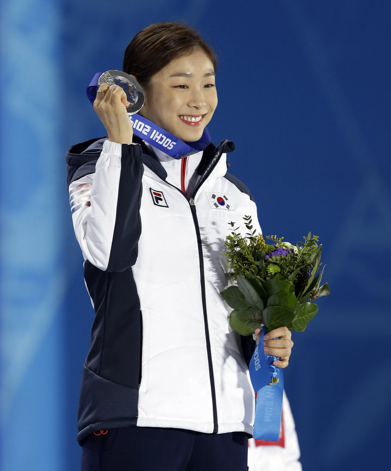 Photo - Women's free skate figure skating silver medalist Yuna Kim of South Korea smiles while holding her medal at the 2014 Winter Olympics, Friday, Feb. 21, 2014, in Sochi, Russia. (AP Photo/Darron Cummings)
