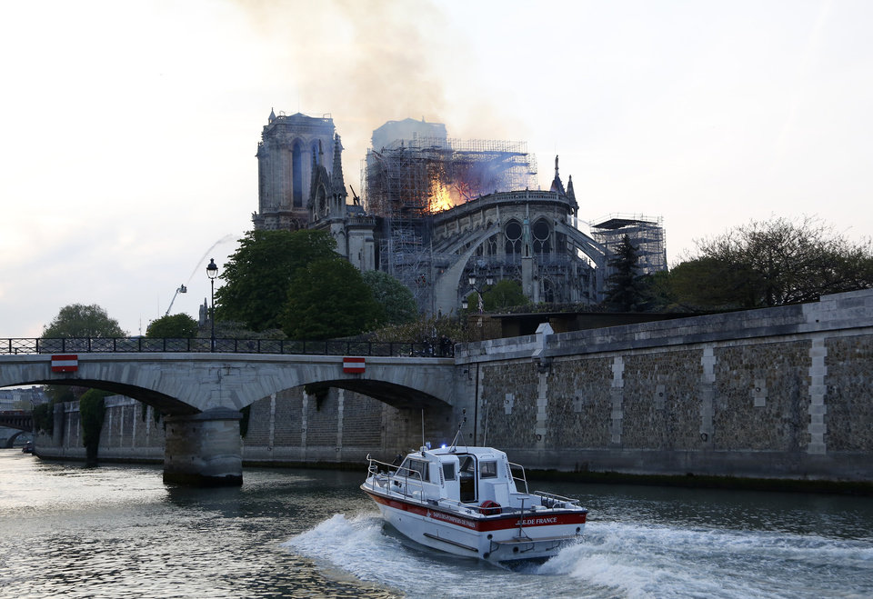 Photo - A speedboat travels down the river Seine as flames and smoke rise from Notre Dame cathedral as it burns in Paris, Monday, April 15, 2019. Massive plumes of yellow brown smoke is filling the air above Notre Dame Cathedral and ash is falling on tourists and others around the island that marks the center of Paris. (AP Photo/Thibault Camus)