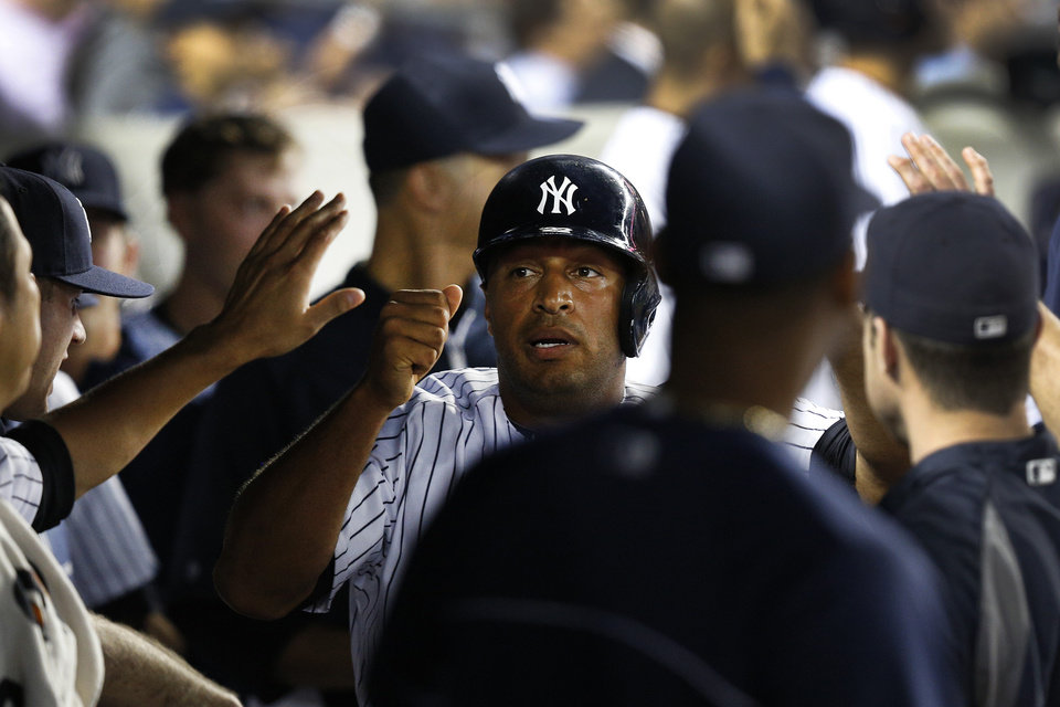 Photo - New York Yankees' Vernon Wells, center, celebrates with teammates in the dugout after stealing home in the second inning of a baseball game against the Chicago White Sox at Yankee Stadium, Tuesday, Sept. 3, 2013, in New York. (AP Photo/John Minchillo)