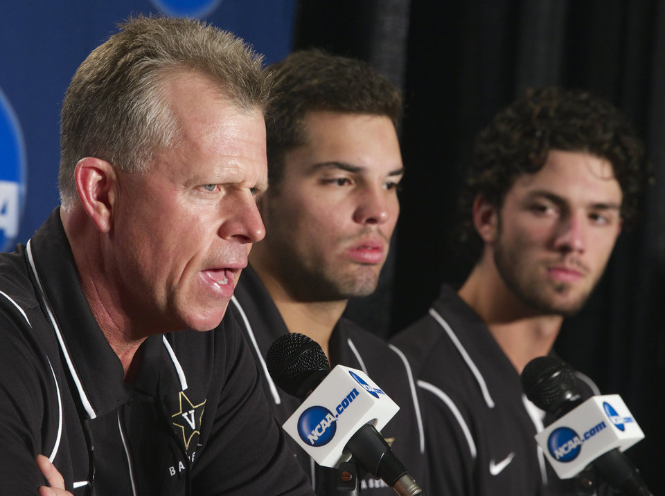 Photo - Vanderbilt coach Tim Corbin, left, speaks at a news conference on Sunday, June 22, 2014, with Virginia players Vince Conde, center, and Dansby Swanson, right, listening before the NCAA baseball College World Series finals between Virginia and Vanderbilt which begin on Monday at TD Ameritrade Park in Omaha, Neb. (AP Photo/Nati Harnik)