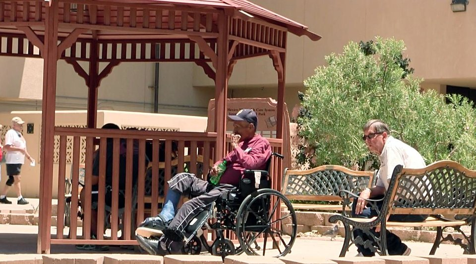 Photo - Men sit outside the Raymond G. Murphy VA Medical Center in Albuquerque, N.M., Thursday, July 3, 2014. A veteran who collapsed in an Albuquerque Veteran Affairs hospital cafeteria 500 yards from the emergency room, died Monday, June 30, 2014, after waiting 30 minutes for an ambulance, officials confirmed Thursday. Officials at the hospital said it took a half an hour for the ambulance to be dispatched and take the man from one building to the other, which is about a five minute walk. (AP Photo/Russell Contreras)