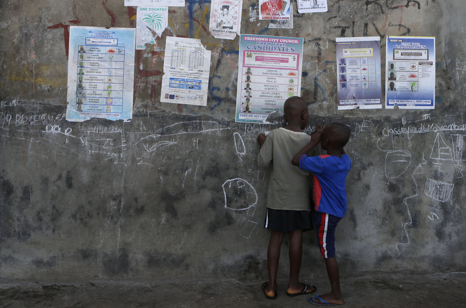 Photo -   Boys draw with chalk on a wall hung with posters displaying sample ballots for the upcoming presidential, parliamentary, and local elections, in Freetown, Sierra Leone Friday, Nov. 16, 2012. Ten years after the end of a devastating civil war, Sierra Leone will go to the polls on Saturday to choose between candidates including incumbent President Ernest Bai Koroma and opposition leader Julius Maada Bio. (AP Photo/Rebecca Blackwell)