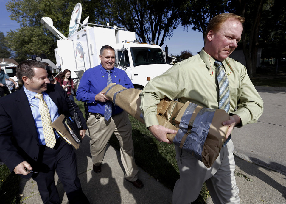 Photo -   Roseville Police Department detectives carry soil samples removed from a shed floor of a Roseville, Mich., home Friday, Sept. 28, 2012. Police have been told by a source that former Teamsters boss Jimmy Hoffa may be buried beneath a driveway. (AP Photo/Paul Sancya)