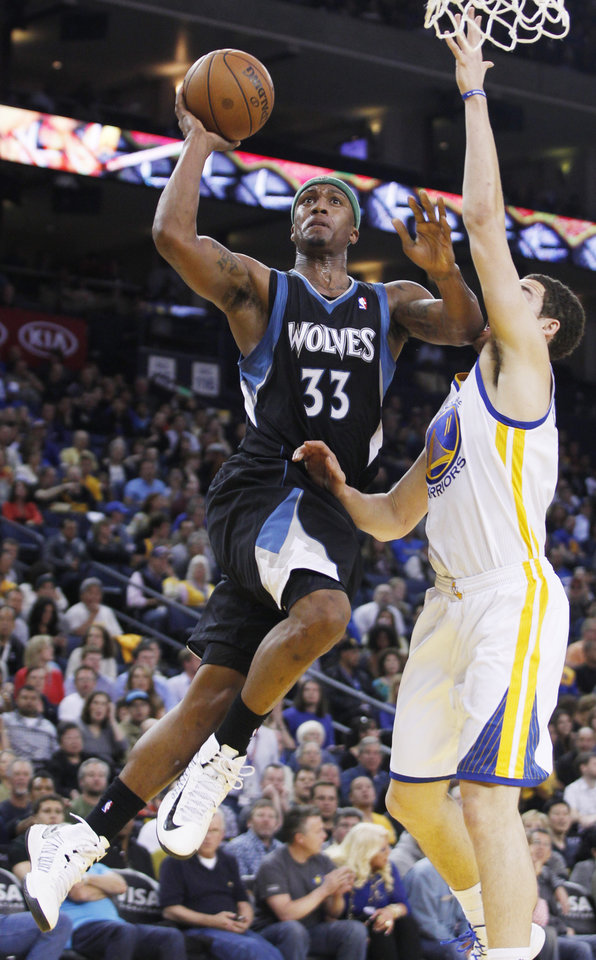 Minnesota Timberwolves' Dante Cunningham shoots as Golden State Warriors' Klay Thompson defends during the first half of an NBA basketball game, Tuesday, April 9, 2013, in Oakland, Calif. (AP Photo/George Nikitin)
