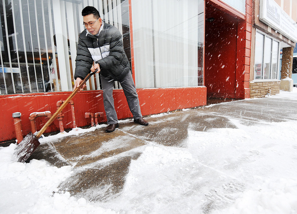 Photo - Duc Nguyen shovels the sidewalk in front of the Great Hunan Restaurant while it snows Thursday, Dec. 20, 2012, in Winona, Minn.  The first major snowstorm of the season began its slow eastward march across the Midwest early Thursday, creating treacherous driving conditions and threatening to disrupt some of the nation's busiest airports ahead of the holiday weekend. (AP Photo/Winona Daily News, Joe Ahlquist)