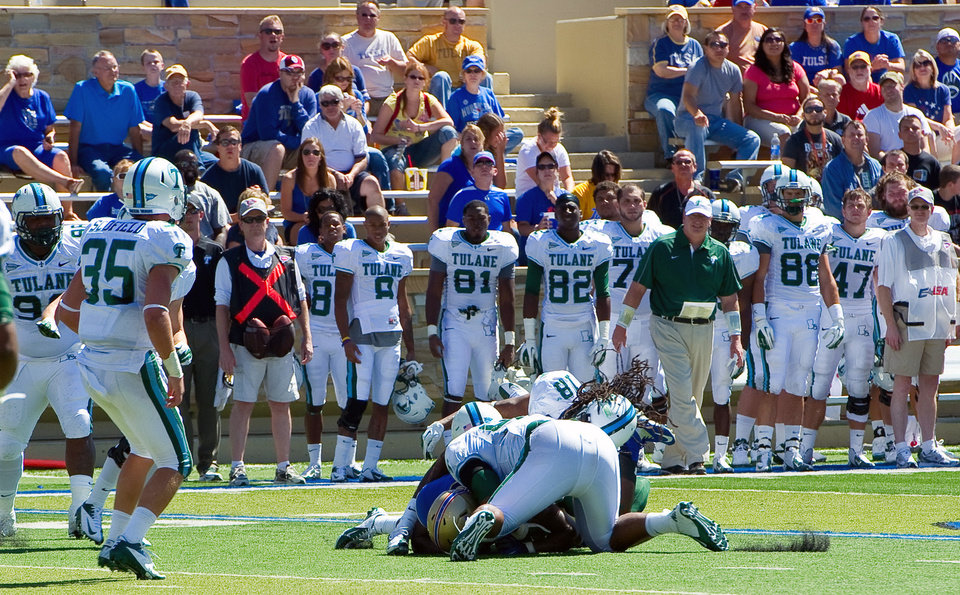 Photo -   In this photo provided by the University of Tulsa, Tulane's Devon Walker (18) and Julius Warmsley (92), center foreground, tackle Tulsa's Kenny Welcome during the first half of an NCAA college football game in Tulsa, Okla., Saturday, Sept. 8, 2012. On this play, Walker was seriously hurt. (AP Photo/University of Tulsa, John Lew)