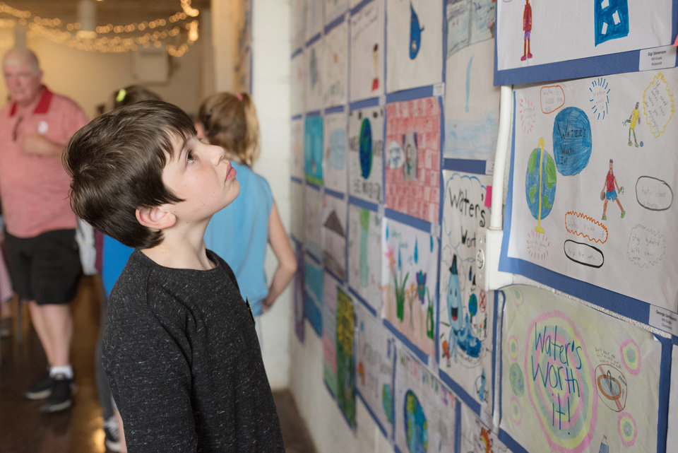 Photo -  Sam Pilat, 10, looks at his art and other submissions at the 2018 Water's Worth It art show put on by the city of Norman Environmental Control Advisory Board ahead of Earth Day. [PHOTO BY WHITNEY BRYEN, FOR THE OKLAHOMAN]