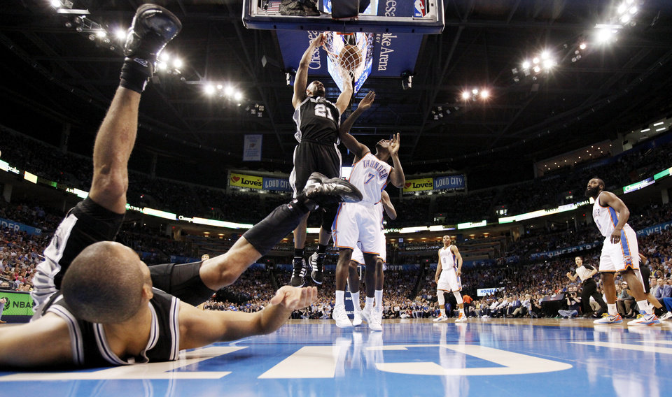 Photo - San Antonio's Tony Parker (9) watches from the ground as Tim Duncan (21) dunks a missed shot by Parker next to Oklahoma City's Royal Ivey (7) during the NBA basketball game between the Oklahoma City Thunder and the San Antonio Spurs at Chesapeake Energy Arena in Oklahoma City, Friday, March 16, 2012. Photo by Nate Billings, The Oklahoman