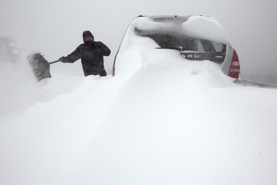 Steve Hull digs out his car after it was covered by drifting snow in Portland, Maine on Saturday, Feb. 9, 2013. A behemoth storm packing hurricane-force wind gusts and blizzard conditions swept through the Northeast overnight. (AP Photo/Robert F. Bukaty)