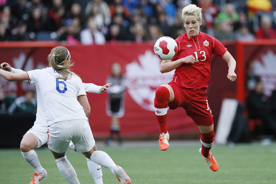 Photo - Canada midfielder Sophie Schmidt (13) knocks the ball down as United States defender Whitney Engen (6) defends during first half of an exhibition soccer match in Winnipeg, Manitoba, Thursday, May 8, 2014. (AP Photo/The Canadian Press, John Woods)