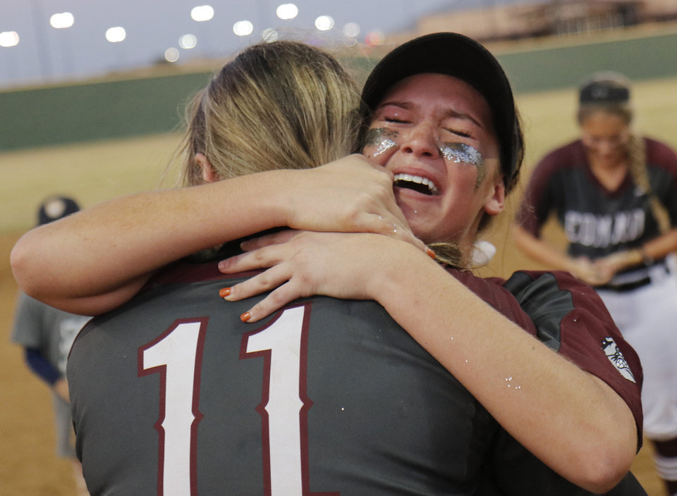 Photo - EHS #14 Mia Holliman hugs pitcher #11 Jill Dickson during the 6A Fast Pitch Championship game between Edmond Memorial and Owasso at the Ball Fields at Firelake in Shawnee, Saturday, October 19, 2019. [Doug Hoke/The Oklahoman]