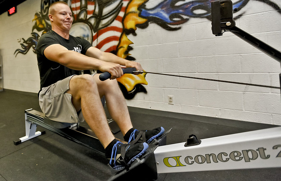 Photo - Randy Dennis works on a rowing exercise machine at Crossfit Native in Warr Acres, Oklahoma. The fitness program helps men and women get in shape before going into the military.  CHRIS LANDSBERGER - CHRIS LANDSBERGER