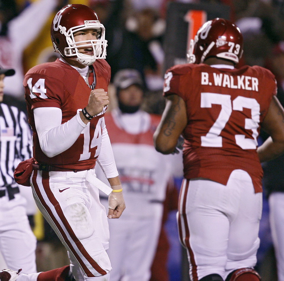 Photo - Oklahoma's Sam Bradford (14) pumps his fist after throwing a touchdown pass during the first half of the Big 12 Championship college football game between the University of Oklahoma Sooners (OU) and the University of Missouri Tigers (MU) on Saturday, Dec. 6, 2008, at Arrowhead Stadium in Kansas City, Mo. 