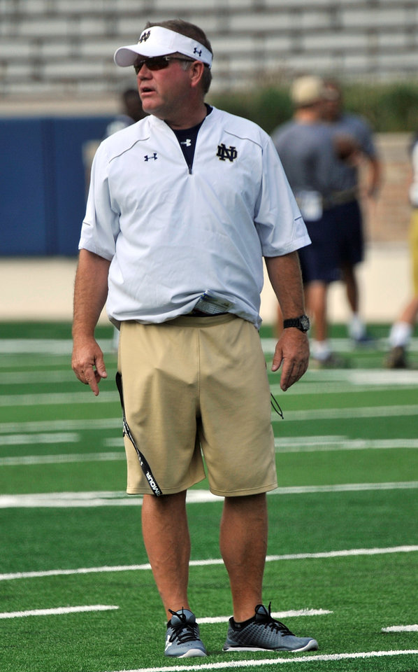 Photo - Notre Dame coach Brian Kelly talks to his players at practice during media day for the NCAA college football team Tuesday Aug. 19, 2014, in South Bend, Ind. (AP Photo/Joe Raymond)