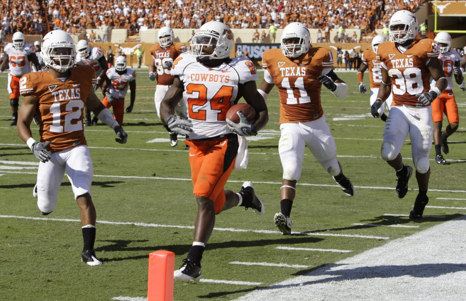 Photo - OKLAHOMA STATE UNIVERSITY / OSU: Oklahoma State running back Kendall Hunter (24) runs for a touchdown as Texas defenders Earl Thomas (12), Jared Norton (11) and Roddrick Muckelroy (38) pursue during the second quarter of an NCAA college football game in Austin, Texas, Saturday, Oct. 25, 2008. (AP Photo/Eric Gay) ORG XMIT: TXEG102