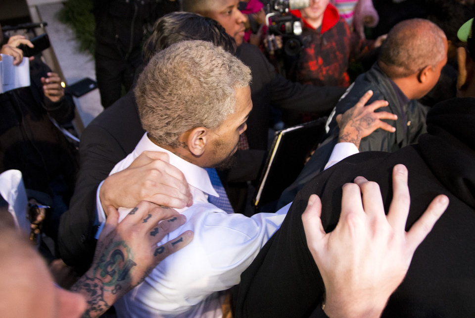 Photo - Singer Chris Brown is surrounded by bodyguards as he departs the H. Carl Moultriel courthouse Monday, Oct. 28, 2013, in Washington. A charge against the Grammy Award-winning R&B singer has been reduced to a misdemeanor and he was ordered released after his arrest Sunday following an altercation outside a Washington hotel. (AP Photo/ Evan Vucci)