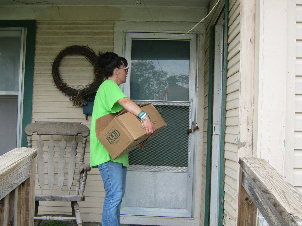 Photo -  Jesus House resident Leslie Stickney, 42, prepares to give a box of food to a homeowner in the Orchard Park neighborhood as part of the Jesus House's Adopt-A-Block program. Photo by Carla Hinton, The Oklahoman