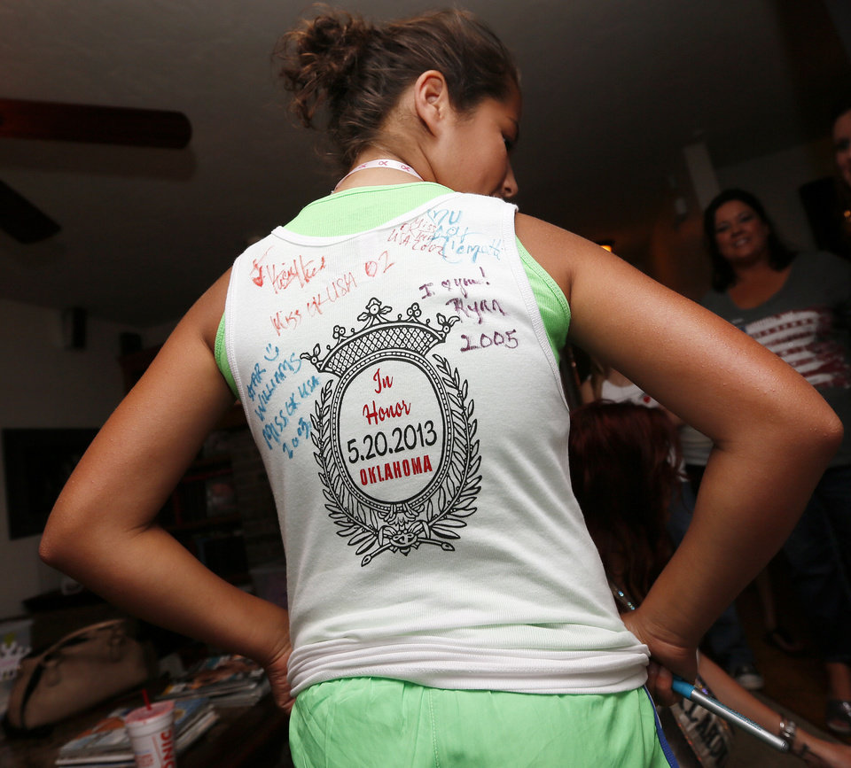 Photo - Karima Merzouk, 12, of Moore, Okla., shows the back of her shirt, which has been autographed by Oklahoma beauty queens, at the end of the