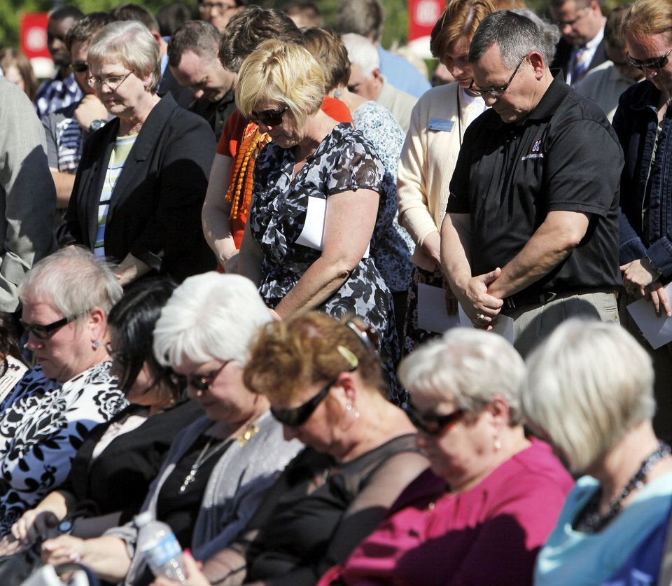 Photo - People pray during the 4/19 - 9/11 Survivor Tree dedication at Oklahoma Christian University.