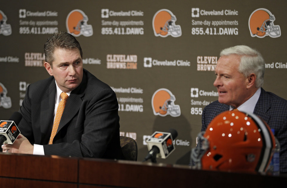 Photo - New Cleveland Browns head coach Rob Chudzinski, left, listens to owner Jimmy Haslam during an news conference at the NFL football team's practice facility in Berea, Ohio Friday, Jan. 11, 2013. Chudzinski, the Carolina Panthers offensive coordinator since 2011, becomes the 14th full-time head coach in franchise history. (AP Photo/Mark Duncan)