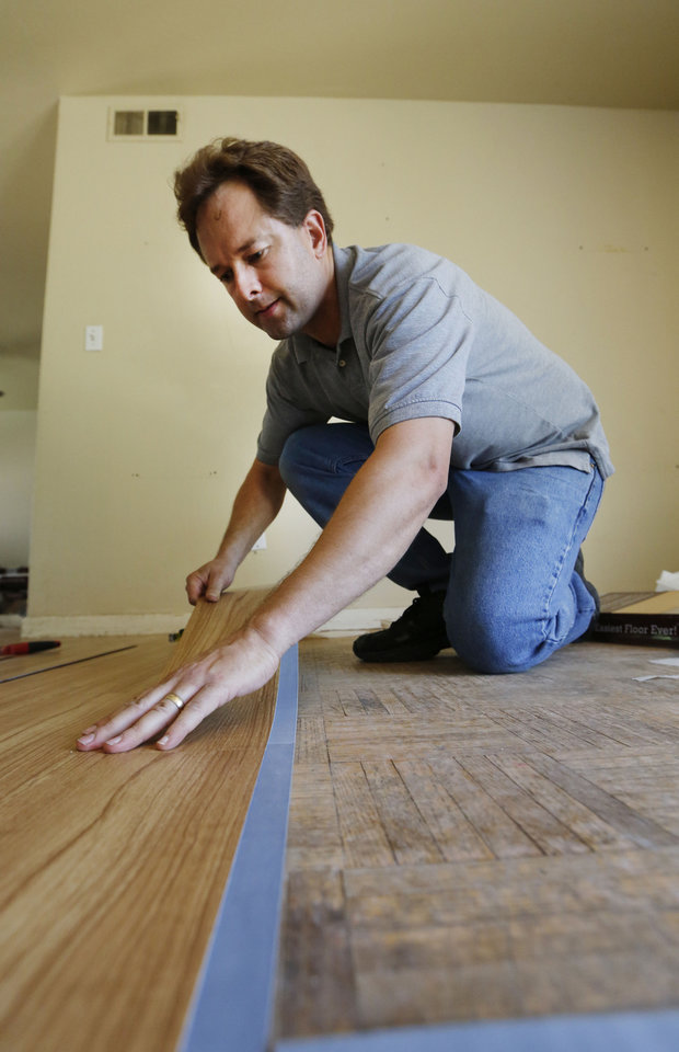 Photo - Val Campbell installs new flooring in the dining room of Iraq War veteran Josh Lozier's home in Midwest City. Campbell and other volunteers from Home Depot were refurbishing Lozier's house. Photo By Steve Gooch, The Oklahoman  Steve Gooch - The Oklahoman