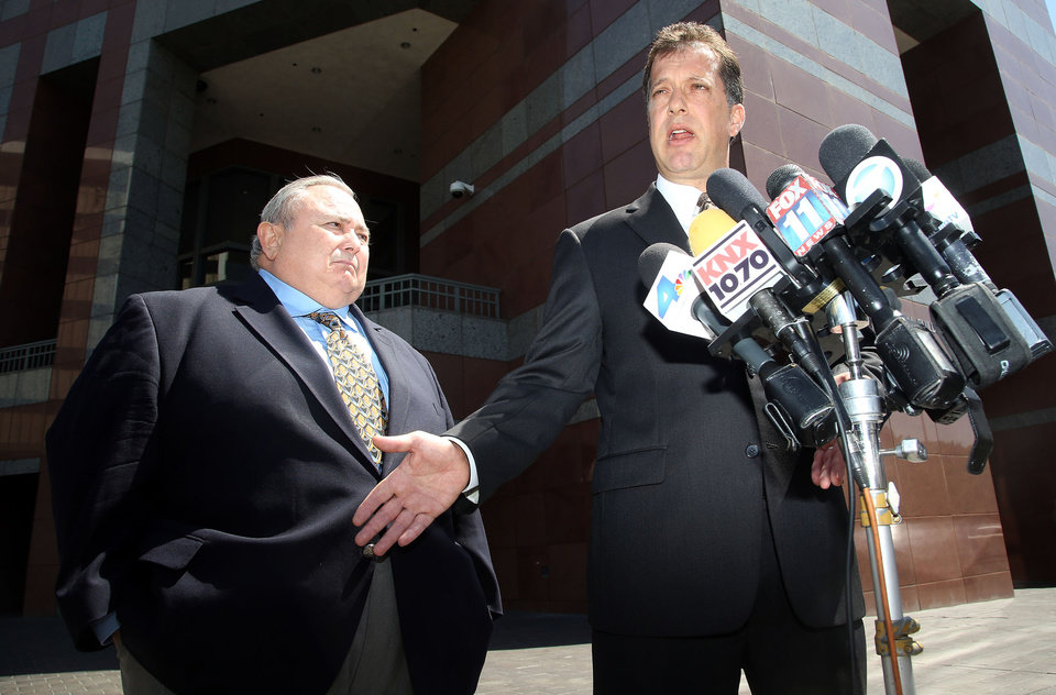 Photo - Former Bell city manager Robert Rizzo, left, and his attorney, James Spertus take questions from the media, as they leave the Edward R. Roybal Federal building and United States courthouse Monday, April 14, 2014. Rizzo was sentenced to 33 months in prison for income tax evasion on Monday. On Wednesday Rizzo faces sentencing in state court on 69 counts of fraud, misappropriation of public funds and other charges for his role in the Bell scandal. He pleaded no contest in that case in October. (AP Photo/Nick Ut)