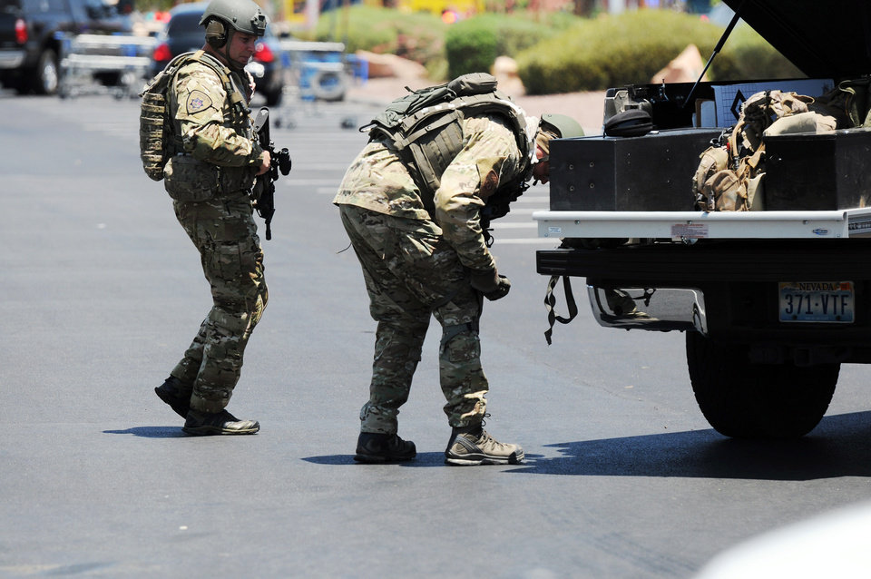 Photo - Las Vegas police officers prepare to go near the scene of a shooting in Las Vegas, Sunday, June 8, 2014. The spree began around 11:30 a.m. Sunday when a man and woman walked into CiCi's Pizza and shot two officers who were eating lunch, Las Vegas police spokesman Larry Hadfield said. (AP Photo/Las Vegas Review-Journal, Eric Verduzco)
