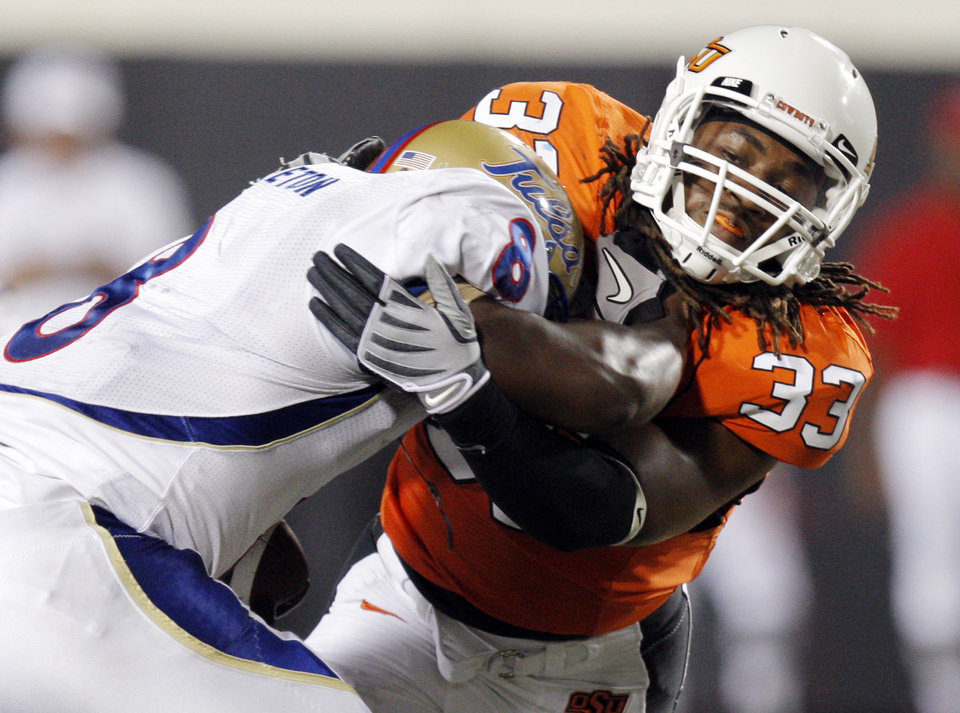 Photo - OSU's LeRon Furr (33) stops TU's Alex Singleton (8) in the third quarter during the college football game between the University of Tulsa (TU) and Oklahoma State University (OSU) at Boone Pickens Stadium in Stillwater, Oklahoma, Saturday, September 18, 2010. OSU won, 65-28. Photo by Nate Billings, The Oklahoman