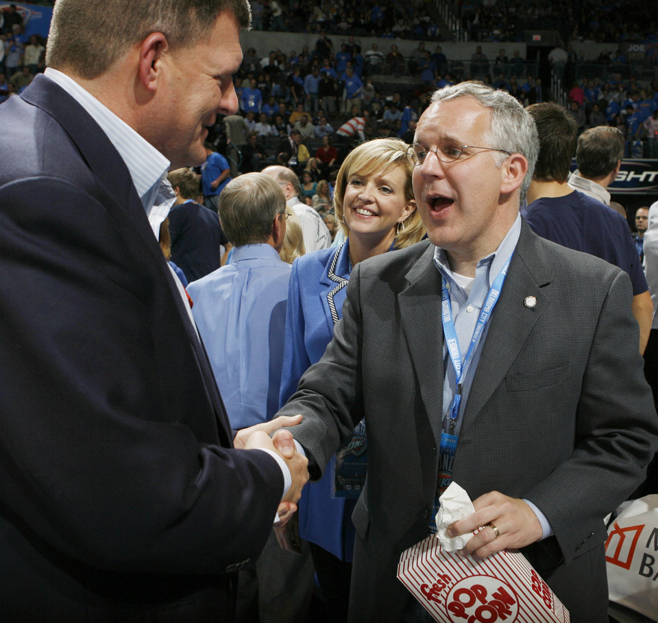 Clay Bennett shakes the hand of Oklahoma Gov. Brad Henry as First Lady Kim Henry looks on during the NBA basketball game between the Oklahoma City Thunder and the Milwaukee Bucks at the Ford Center in Oklahoma City, Wednesday, Oct. 29, 2008. This was the regular season debut of the Thunder. BY NATE BILLINGS, THE OKLAHOMAN