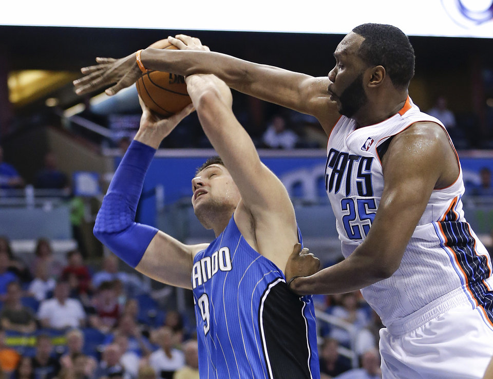 Photo - Charlotte Bobcats center Al Jefferson (25) fouls Orlando Magic's Nikola Vucevic (9) during the second half of an NBA basketball game in Orlando, Fla., Friday, March 28, 2014. Orlando won in overtime, 110-105. (AP Photo/John Raoux)