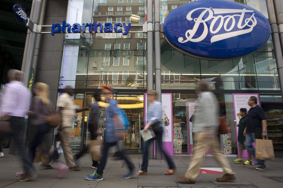 Photo - People walk past the Boots flagship store,  owned by Swiss health and beauty retailer Alliance Boots, on Oxford Street in London, Wednesday, Aug. 6, 2014.  Walgreen plans to keep its roots firmly planted in the United States, saying it will no longer pursue an overseas reorganization that would have trimmed the amount of U.S. taxes it pays.  The nation's largest drugstore chain said that, as previously planned, it will buy the remaining stake in Alliance Boots that it does not already own. It will not pull off an inversion, however, a tactic that has become increasingly popular with U.S. companies seeking tax relief, but which has sparked a backlash in Washington and among the public.  (AP Photo/Matt Dunham)