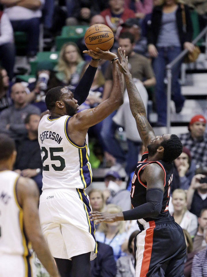 Photo - Utah Jazz's Al Jefferson (25) shoots as Portland Trail Blazers' J.J. Hickson (21) defends in the first quarter during an NBA basketball game Monday, April 1, 2013, in Salt Lake City.  (AP Photo/Rick Bowmer)