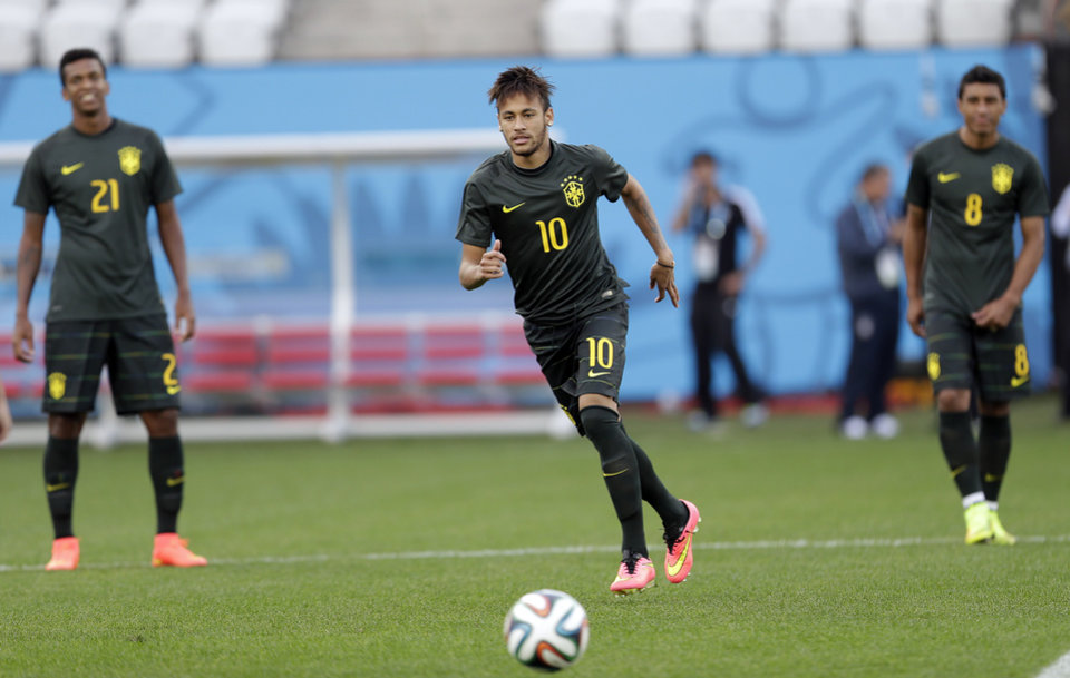 Photo - Brazil's Neymar , center, runs for the ball during an official training session the day before the group A World Cup soccer match between Brazil and Croatia in the Itaquerao Stadium, Sao Paulo       , Brazil, Wednesday, June 11, 2014.  (AP Photo/Andre Penner)