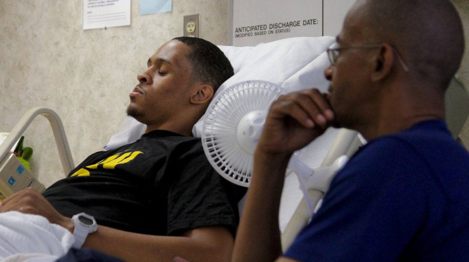 Photo - Norman Richards Sr. listens to his son, Bricktown shooting victim Norman Richards II, in a room at Jim Thorpe Rehabilitation Hospital just before he was discharged on Friday, June 22, 2012.  Photo by Chris Landsberger, The Oklahoman  CHRIS LANDSBERGER - CHRIS LANDSBERGER