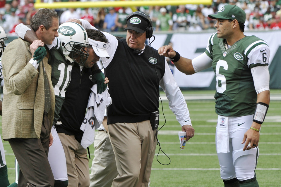 Photo -   New York Jets wide receiver Santonio Holmes (10) is helped off the field as New York Jets head coach Rex Ryan, second from right, and Mark Sanchez (6) show their support during the second half of an NFL football game against the San Francisco 49ers Sunday, Sept. 30, 2012, in East Rutherford, N.J. The Jets lost the game 34-0. (AP Photo/Bill Kostroun)