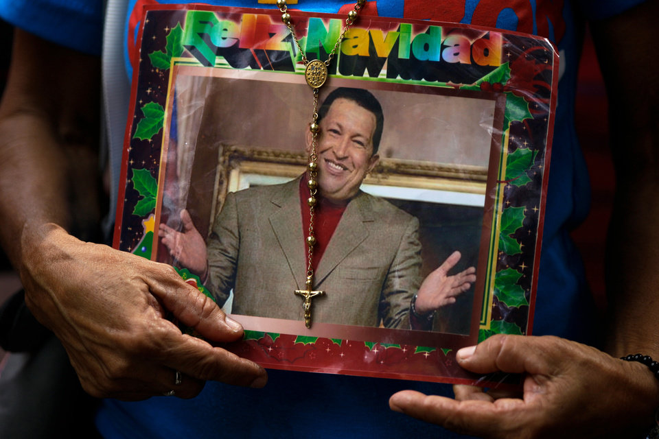 Photo - A supporter of Venezuela's President Hugo Chavez holds a picture of him decorated with a rosary and the words in Spanish