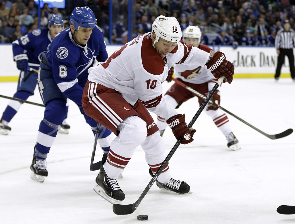 Photo - Phoenix Coyotes right wing David Moss (18) controls the puck in front of Tampa Bay Lightning defenseman Sami Salo (6), of Finland, during the first period of an NHL hockey game, Monday, March 10, 2014, in Tampa, Fla. (AP Photo/Chris O'Meara)
