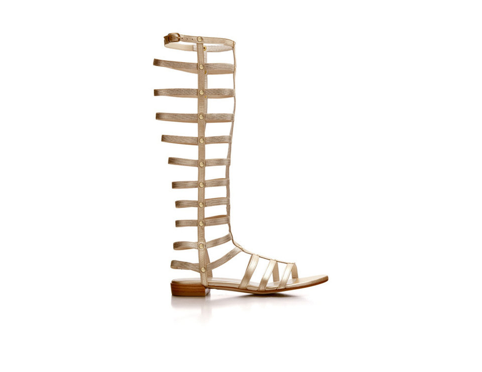 Stuart Weitzman\'s up-to-the-knee flat gladiator makes a striking comeback this spring season in black nappa & gold nappa.