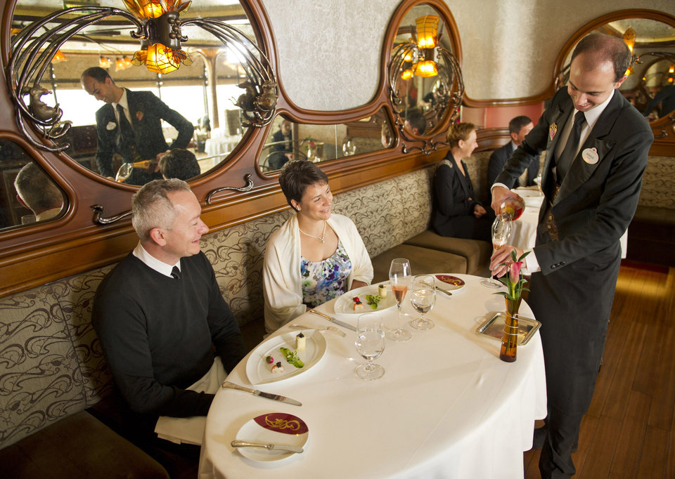 Photo - This 2012 photo released by Disney shows a couple enjoying a champagne brunch at Remy, the adults-only restaurant on Disney's Fantasy and Dream ships. The $50 per person brunch  is part of a continuing trend in the cruise ship industry for upscaled and expanded specialty food options, many of which carry extra fees. (AP Photo/Disney, Kent Phillips)