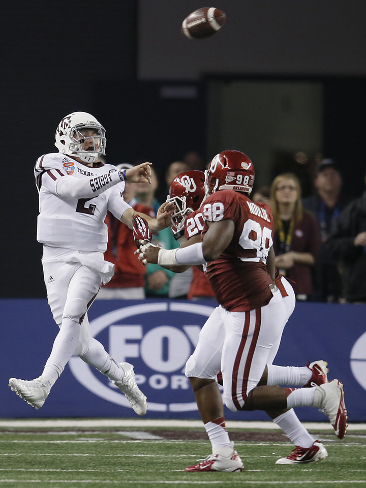 Photo - Texas A&M's Johnny Manziel (2) throws a pass over Oklahoma's Frank Shannon (20) and Chuka Ndulue (98) during the college football Cotton Bowl game between the University of Oklahoma Sooners (OU) and Texas A&M University Aggies (TXAM) at Cowboy's Stadium on Friday Jan. 4, 2013, in Arlington, Tx. Photo by Chris Landsberger, The Oklahoman