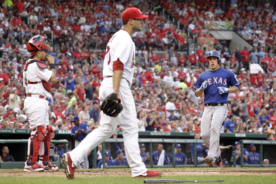 Photo - Texas Rangers' Derek Holland, right, scores on a two-run single by Elvis Andrus as St. Louis Cardinals catcher Yadier Molina, left, and starting pitcher Tyler Lyons, center, look on during the second inning of a baseball game on Friday, June 21, 2013, in St. Louis. (AP Photo/Jeff Roberson)
