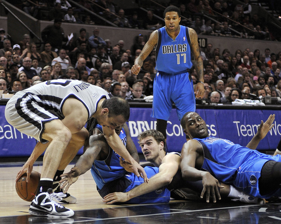 Photo - San Antonio Spurs' Manu Ginobili, left, of Argentina, and Tiago Splitter, center right, of Brazil, scrap for a loose ball against Dallas Mavericks' Elton Brand, right, and Jae Crowder as Mavericks' Chris Douglas-Roberts, rear, watches during the first half of an NBA basketball game, Sunday, Dec. 23, 2012, in San Antonio. (AP Photo/Darren Abate)
