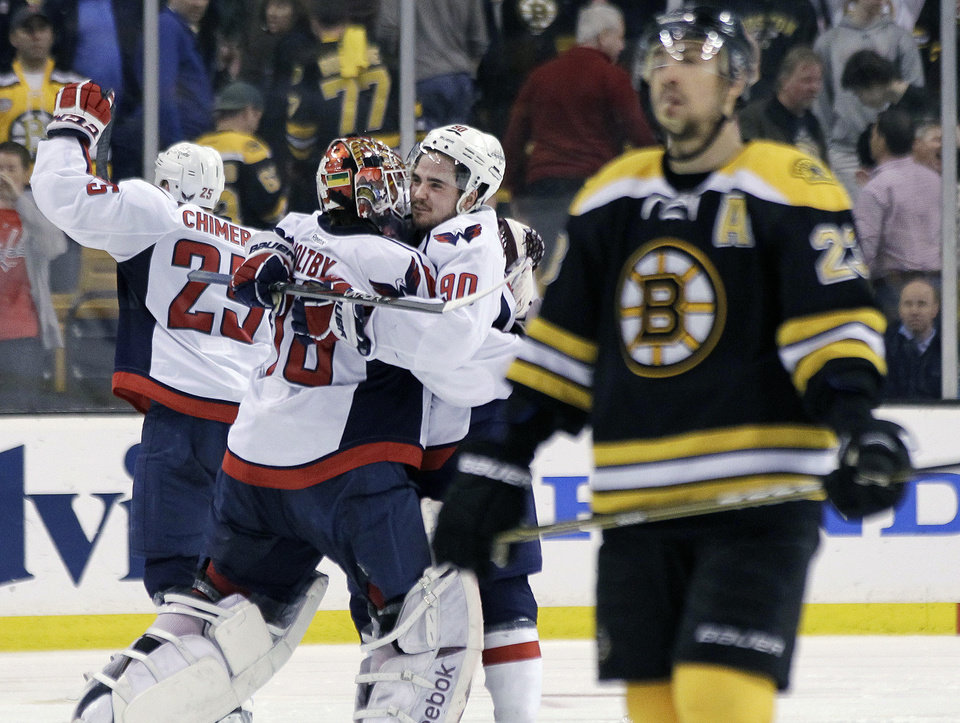 Photo -   Boston Bruins center Chris Kelly (23) skates away as Washington Capitals goalie Braden Holtby (70); center Marcus Johansson (90), of Sweden; and left wing Jason Chimera (25) celebrate the Capitals' 2-1 win in overtime in Game 7 of an NHL hockey Stanley Cup first-round playoff series, in Boston on Wednesday, April 25, 2012. (AP Photo/Elise Amendola)